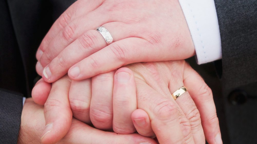 Two men holding hands with wedding rings