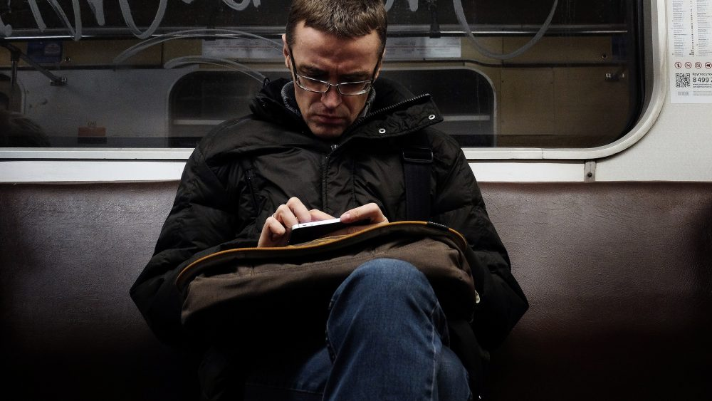 A man reads using his smartphone on the subway