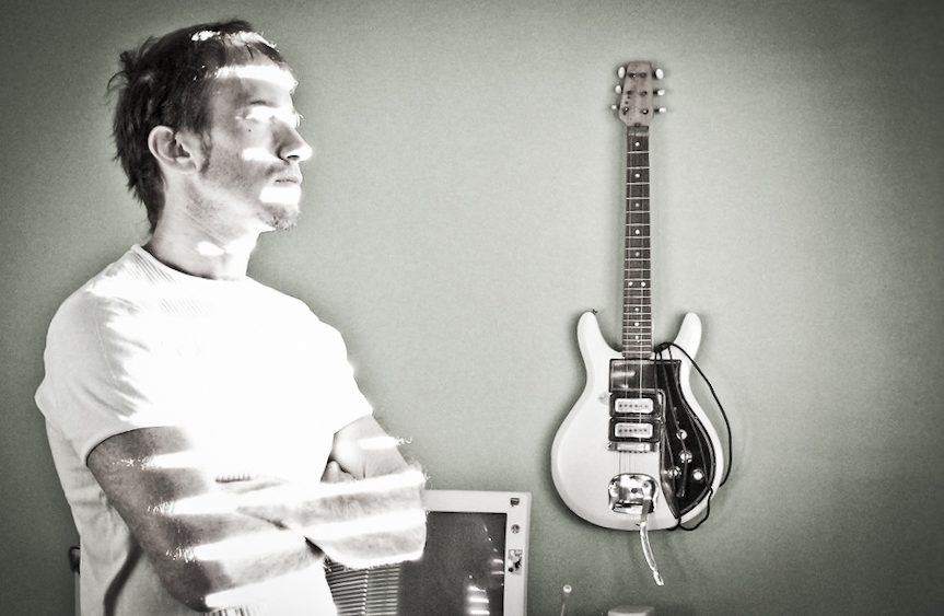 A young man stares into the distance, with a guitar in the background