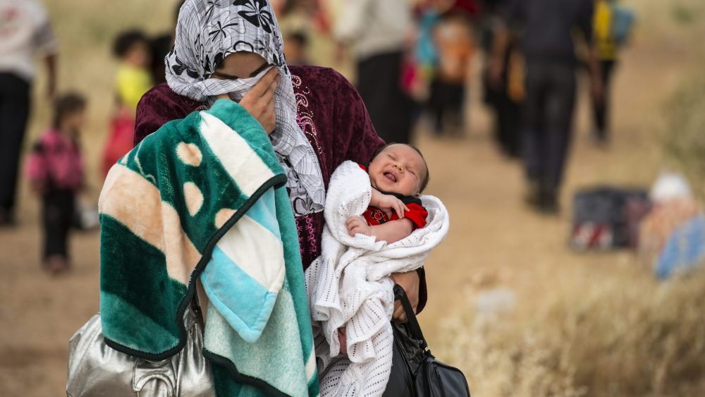 "A young mother crosses the border from Syria and becomes a refugee. She carries her one-month-old son, Hamid. ""Since he was born there has been non-stop bombing every day."""