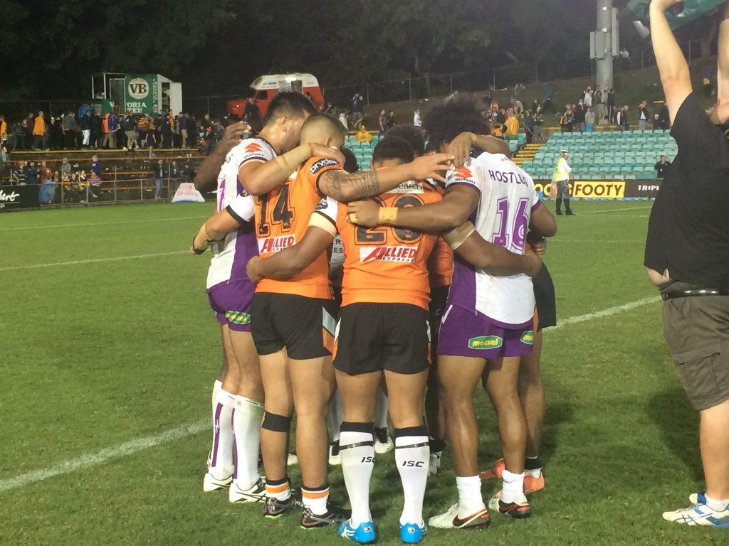 NRL players praying after a match