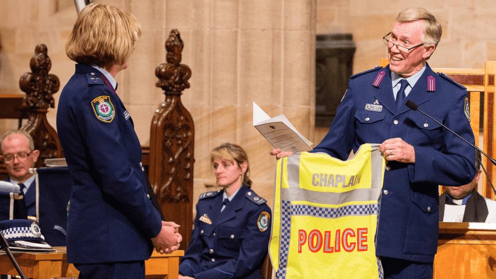 Senior State Chaplain David Riethmuller hands Rev Sarah Plummer her police chaplain vest