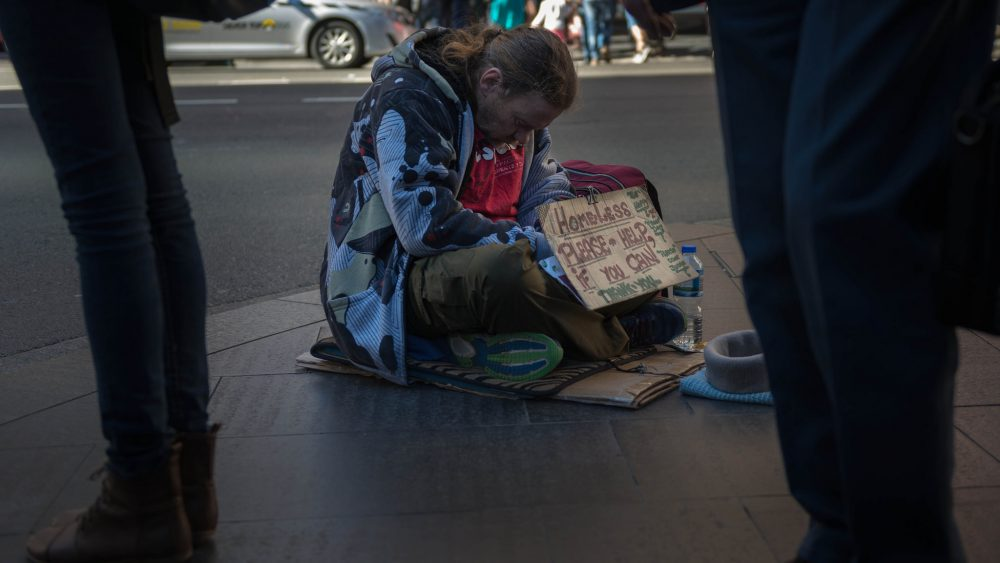 A homeless person begs on the streets of Sydney