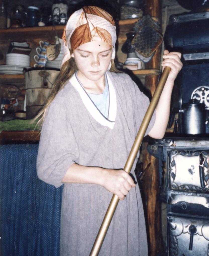 Elishaba sweeps the floor of the family cabin