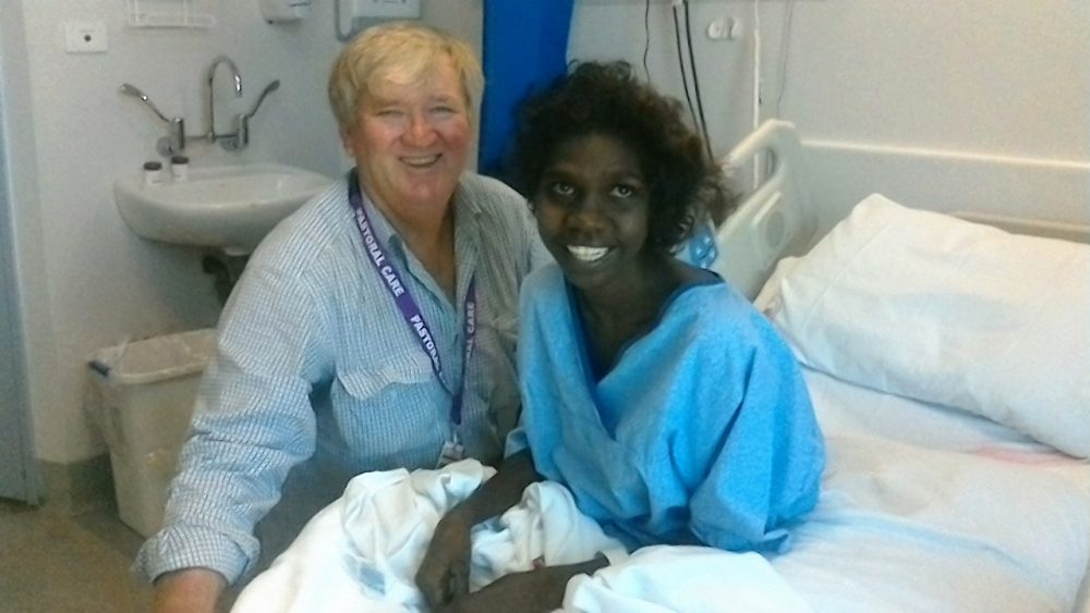 Hospital chaplain Jeff Godwell cheers up an Aboriginal patient at Townsville Hospital.