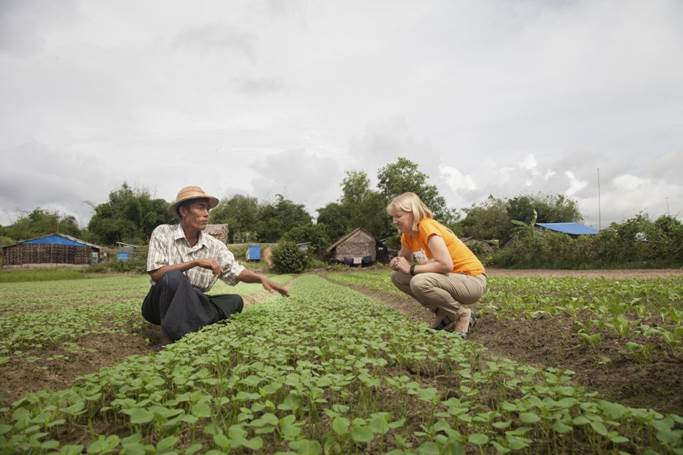 A farmer explains to Claire Rogers how he has been able to increase his yield through the initiatives of World Vision's agricultural and livelihoods program supported by the Australian Government.