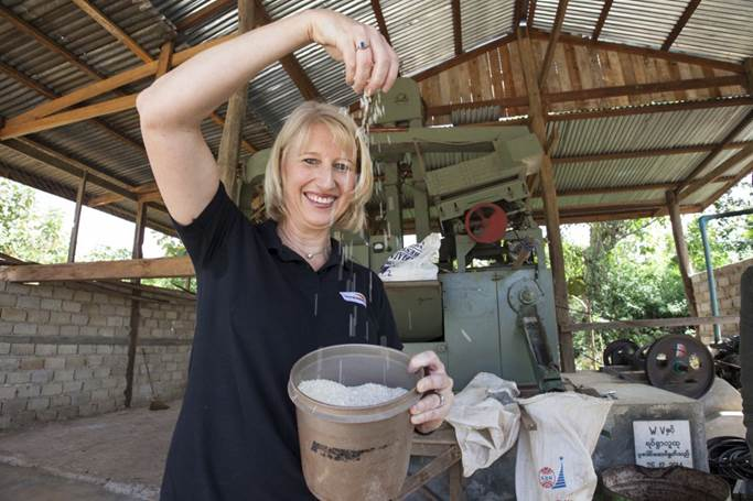The new CEO admires the rice produced from a mill which World Vision Australia helped the local community establish