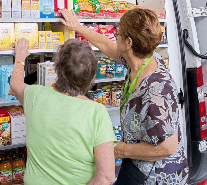 An Anglicare volunteer helps a woman select her groceries