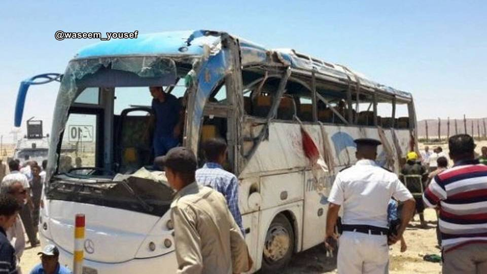 Police inspect a bus that was attacked south of Cairo on Friday