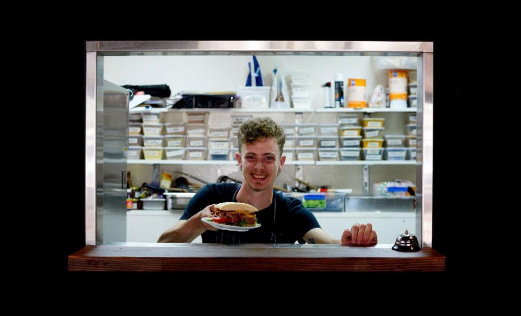 Finn, Hope Street Café staff, serves up a meal with a smile