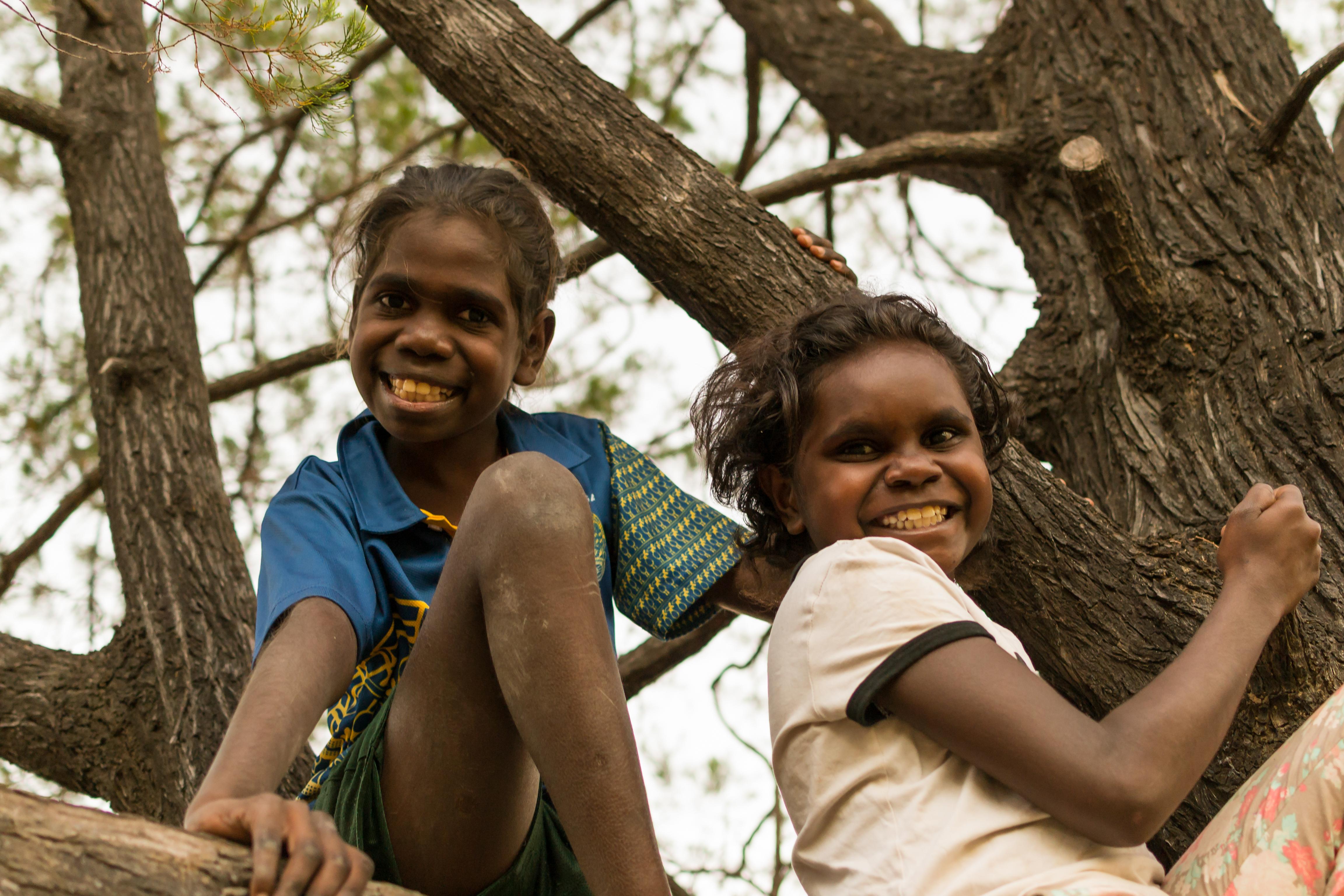 Two girls play in the tree before Kids Club, Barunga