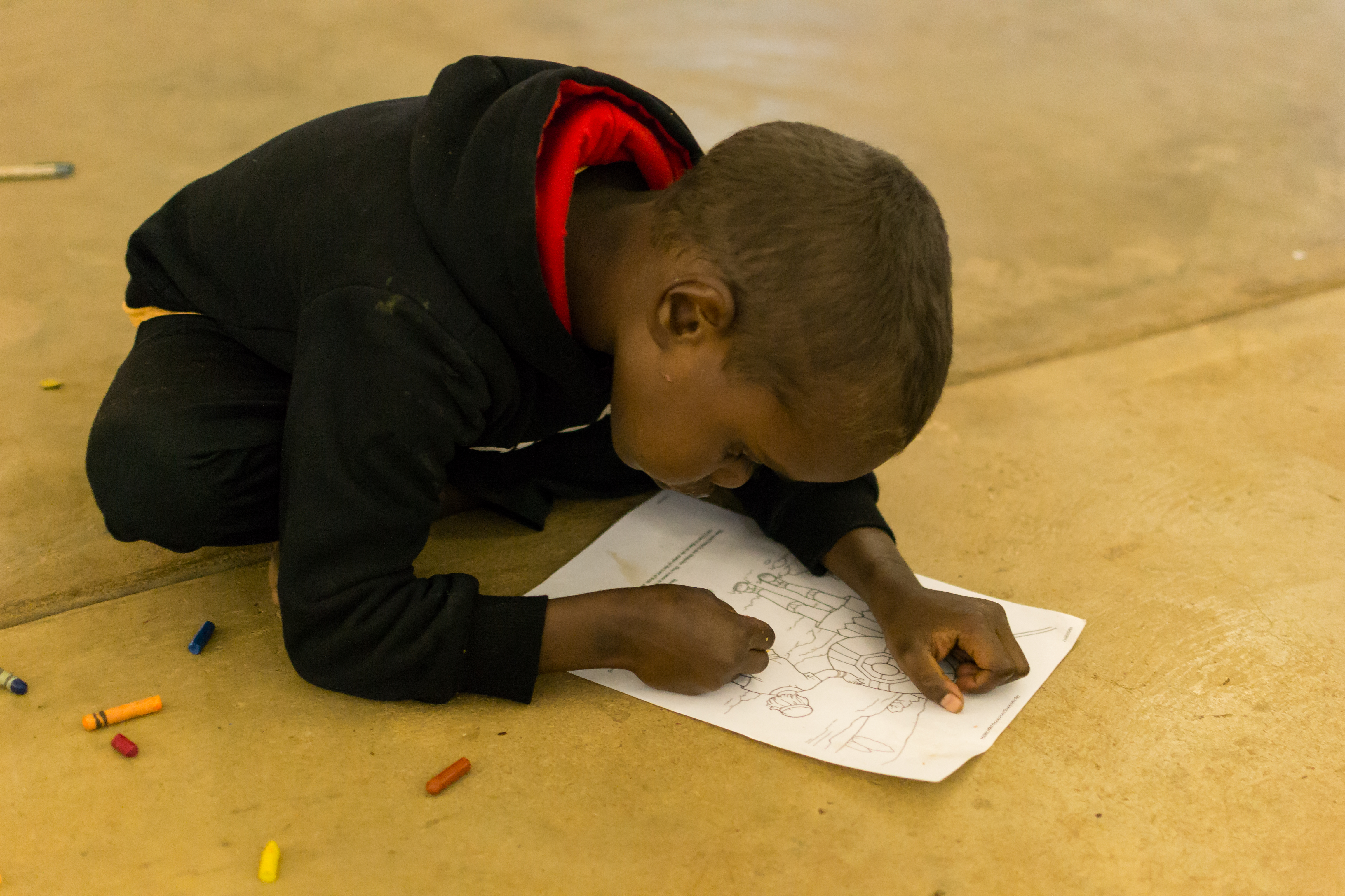 A child colours in at Kids Club, Barunga