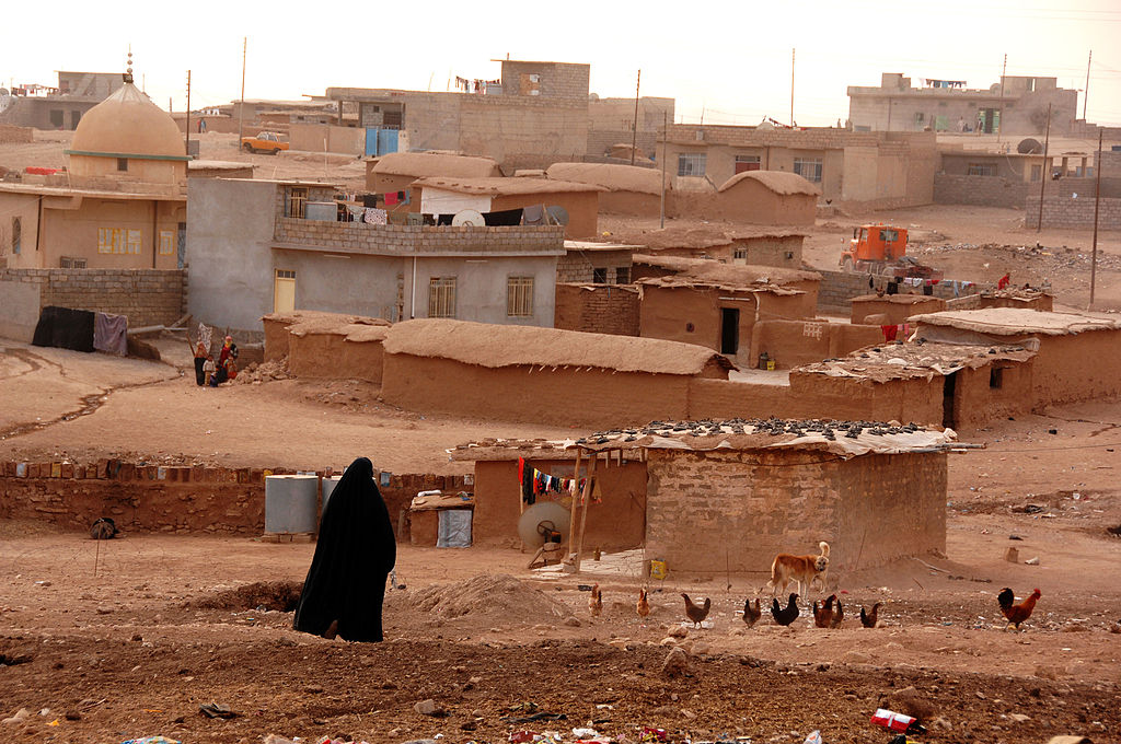 A woman walks through her village outside of Mosul, Iraq