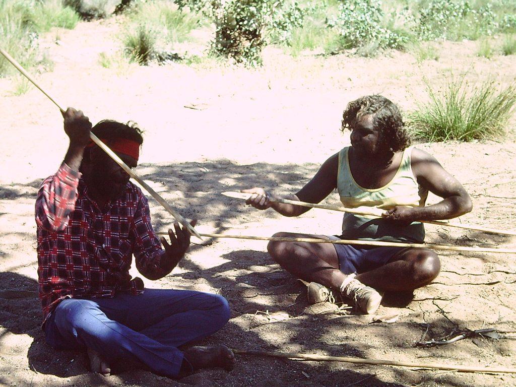 Men check their spears near Uluru