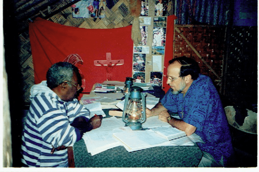 Joseph Mala and John Harris translating by the light of a hurricane lantern