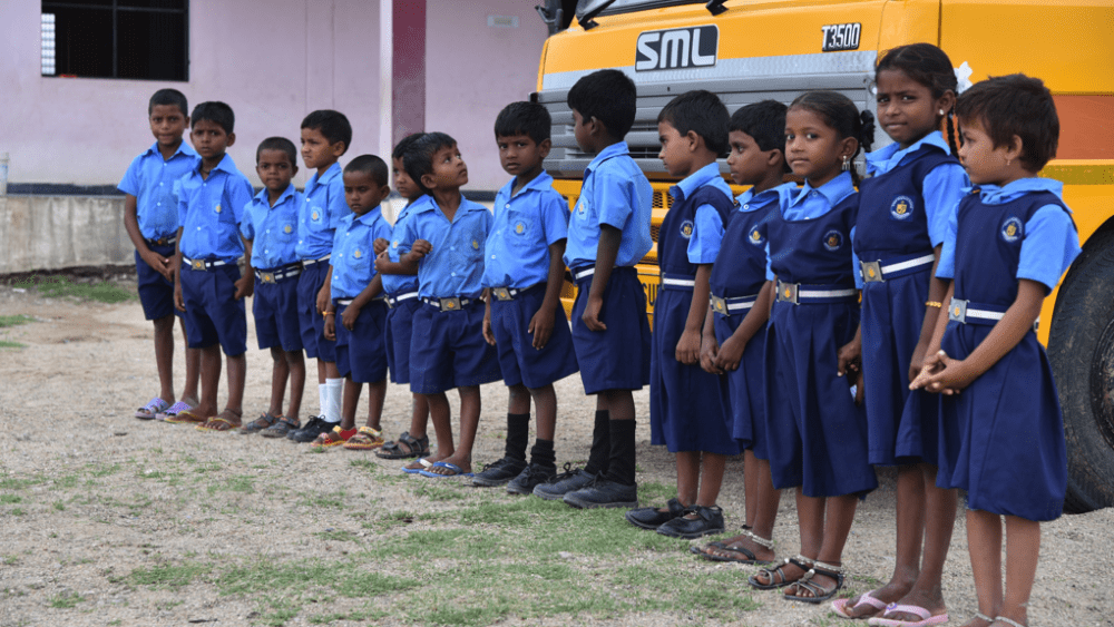 Children in front of their new school bus, August 2017.