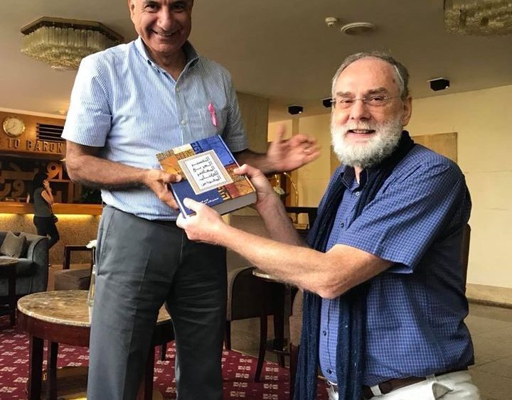 Riad Kassis, left, receives a copy of the Arabic Contemporary Bible Commentary in Cairo last October.