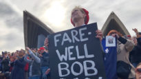 Woman holds farewell sign for Bob Hawke on Opera House foreshore