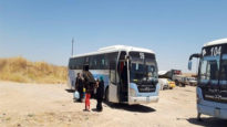 Displaced people board a bus to return to their home areas across Nineveh province in July 2019