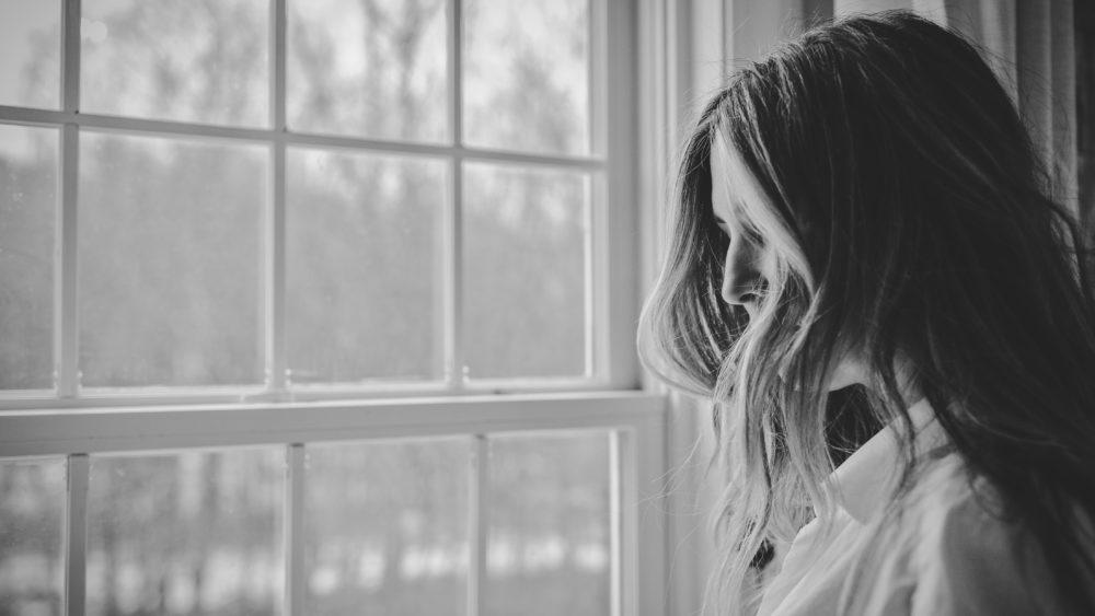 Woman looks out window. Image: Danielle MacInnes/ Unsplash