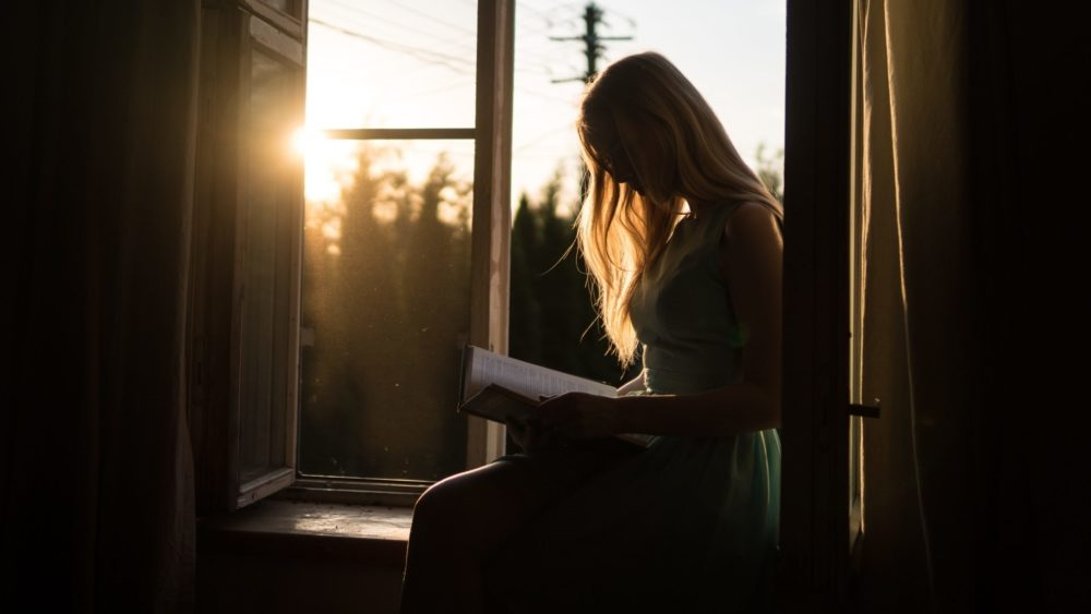 Girls sits in bedroom window with book. Image: Yuri Efremov/ Unsplash