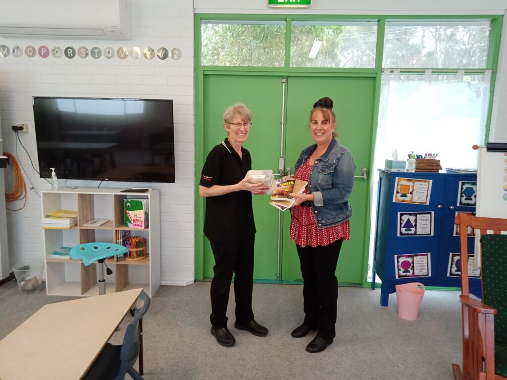CRU staff member Katrina gives meal packs to Tina, principal of a local school.